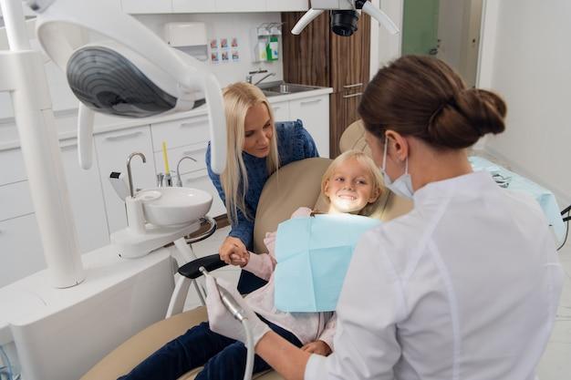 Mamma e sua figlia che visitano uno specialista dentale pediatrico