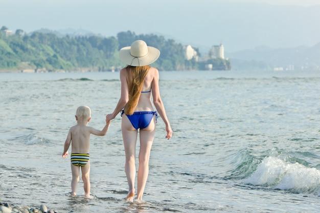 Mamma e suo figlio piccolo stanno camminando lungo la costa del mare. vista posteriore
