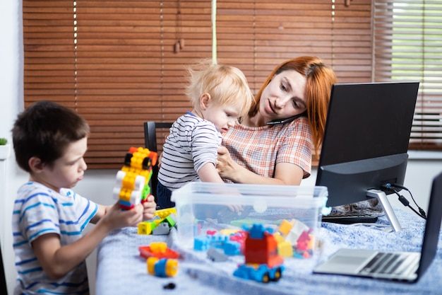 Mamma giovane donna parlando al telefono e cercando di lavorare a un computer a un lavoro remoto durante il periodo di autoisolamento in relazione alla pandemia di coronavirus, soft focus.