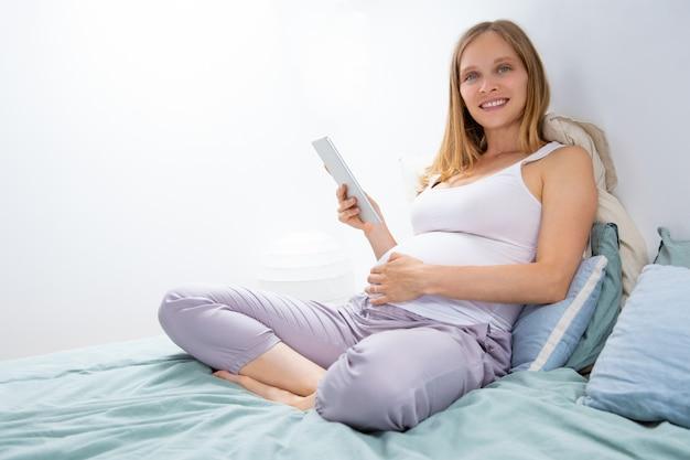 Mamma incinta felice con la compressa che si rilassa nella camera da letto