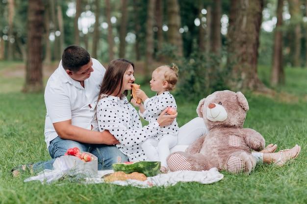 Mamma, papà e figlia piccola sul picnic con l'orsacchiotto nel parco all'aperto. il concetto di vacanza estiva. festa della mamma, del papà, del bambino. famiglia trascorrere del tempo insieme sulla natura. aspetto familiare