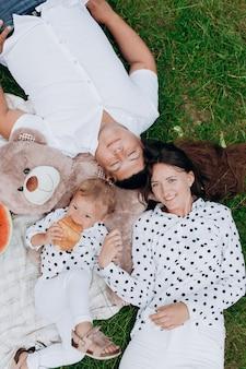Mamma, papà e figlia sdraiato sul picnic con orsacchiotto. il concetto di vacanza estiva. festa della mamma, del papà, del bambino. famiglia trascorrere del tempo insieme sulla natura. aspetto familiare