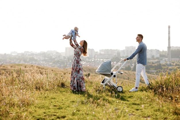 Mamma, papà e piccola donna divertirsi all'aperto nell'erba in giornata estiva. festa della mamma, del papà e del bambino. famiglia felice per una passeggiata con passeggino fuori città.