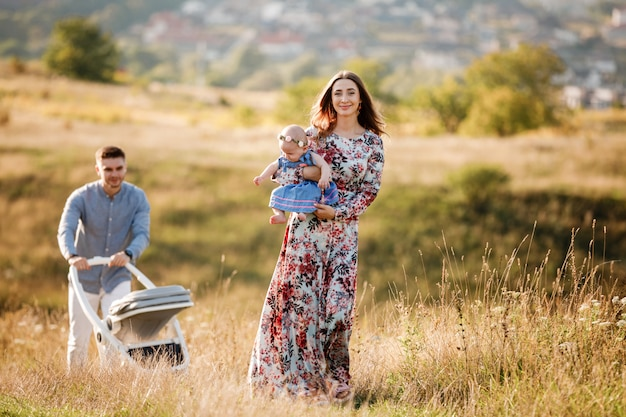 Mamma, papà e piccola donna divertirsi all'aperto nell'erba in giornata estiva. festa della mamma, del papà e del bambino.