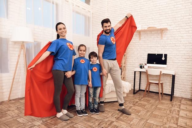 Mamma, papà, figlia e figlio vestiti di supereroi.