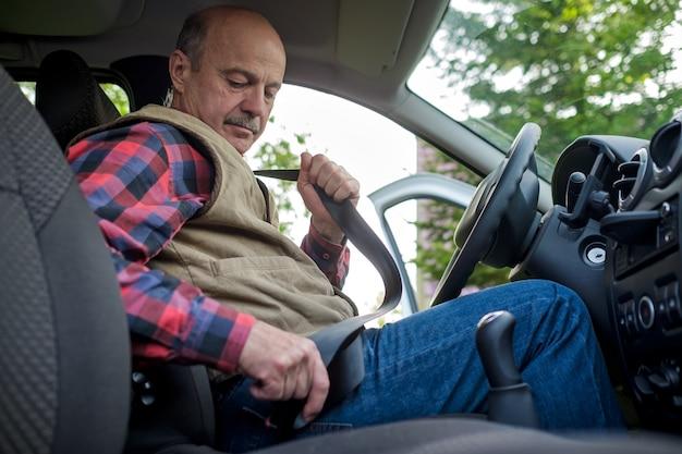 Man cintura di sicurezza di fissaggio prima di guidare
