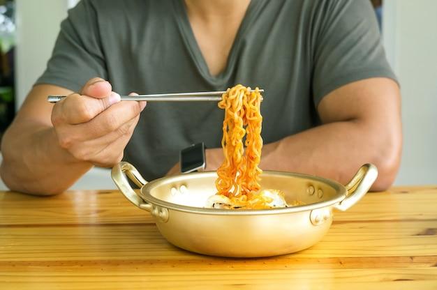 Man eating instant noodle in una mensa.