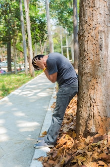 Man facepalm.man facepalming vicino al grande albero quando era povero finanziario e rotti sentire