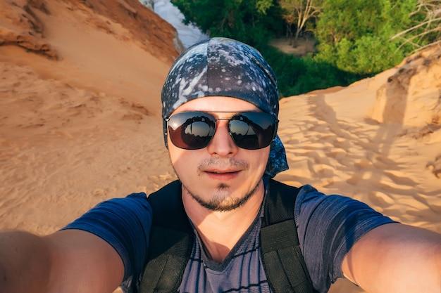 Man hiking fa un selfie sul viso della fotocamera in occhiali da sole e una bandana