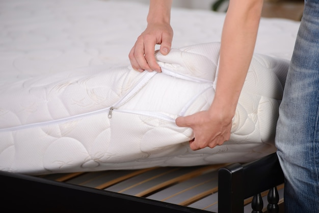 Man holding dimostrazioni materasso di qualità in camera da letto.