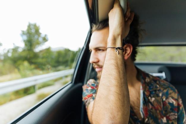 Man holding maniglia in auto