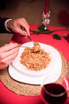 Man mangiare la pasta al tavolo festivo