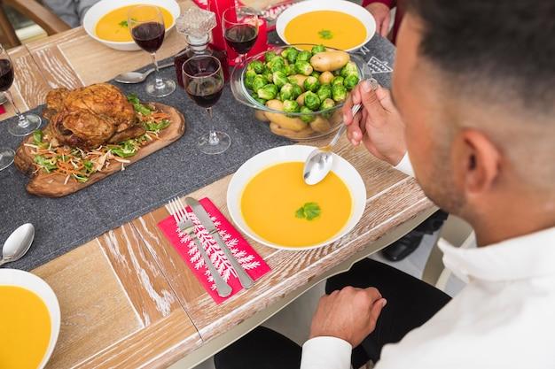 Man mangiare zuppa al tavolo festivo