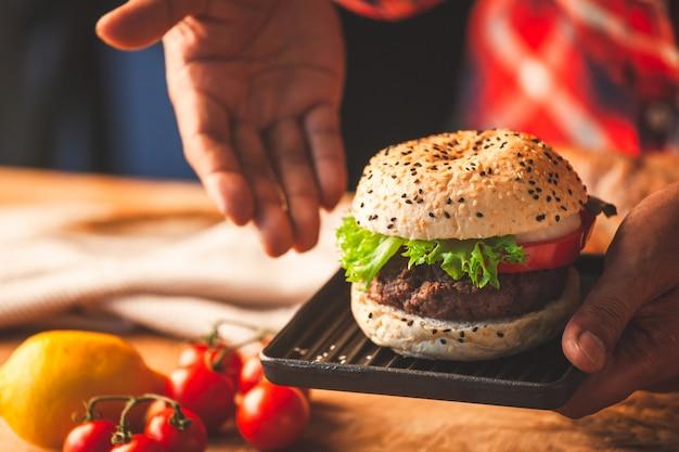 Man mano che tiene delizioso hamburger fatti in casa con verdure fresche, pronti a servire e mangiare