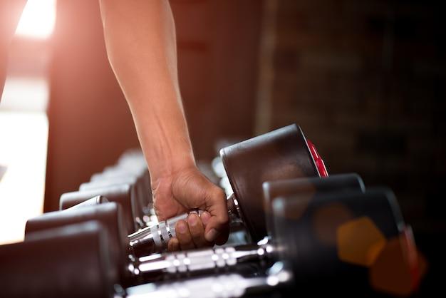 Man mano che tiene il manubrio nel bodybuilding palestra. esercizio e concetto di stile di vita sano.