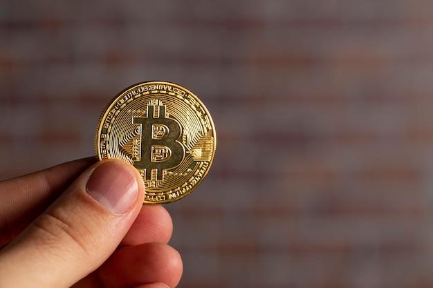 Man mano che tiene un bitcoin fisico davanti a un muro di mattoni