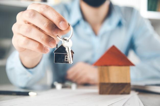 Man mano chiave di casa e modello di casa sulla scrivania