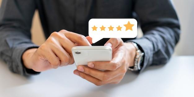 Man mano premere sullo schermo dello smartphone con feedback di valutazione a cinque stelle d'oro