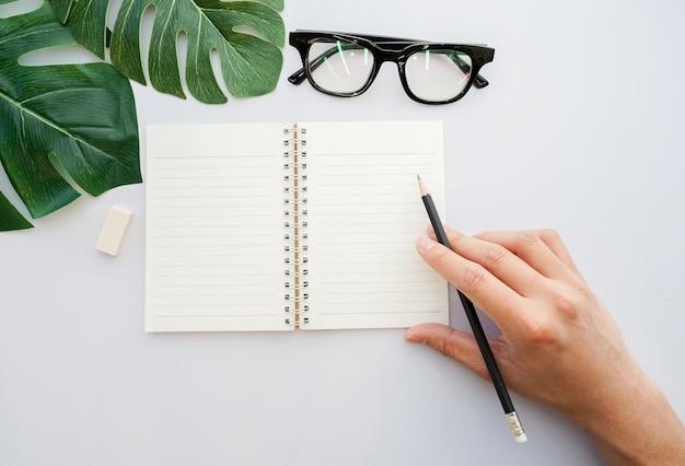Man mano usando la matita nera e preparati a scrivere su mock up notebook in vista dall'alto