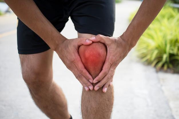 Man runner jogging subisce un infortunio al ginocchio