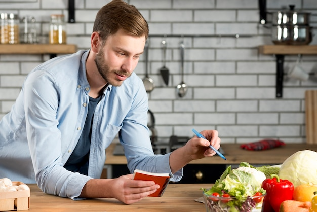 Man scrittura ricetta o dieta vegetale sul suo diario a spirale