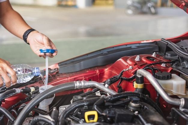Man servizio meccanico manutenzione ispezione servizio manutenzione auto controllare il motore con acqua di riempimento aggiungere acqua al tergicristallo in garage