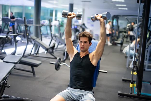 Man sollevamento manubri per allenare le braccia e le spalle in una palestra