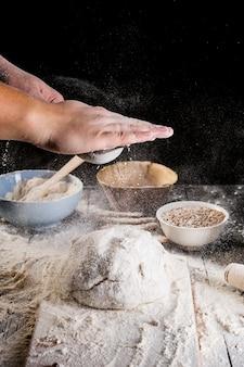 Man spolverata di farina sulla pasta fresca sul tavolo della cucina