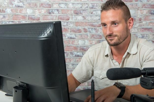 Man video editor con computer e videocamera professionale