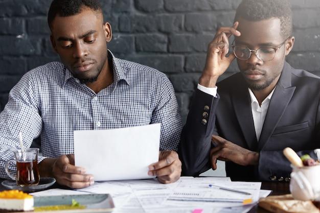 Manager afro-americano con gli occhiali e il suo collega che hanno sguardi stanchi e stressati
