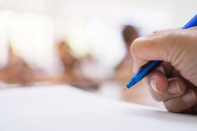 Manager dell'uomo d'affari che tiene penna blu per la firma del documento