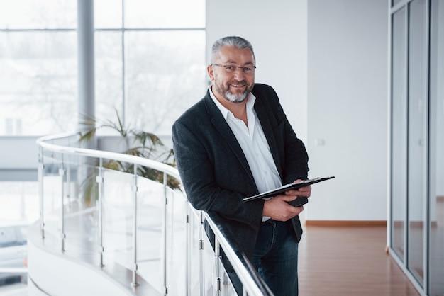Manager di successo. lo puoi vedere dal suo sorriso sincero. foto dell'uomo d'affari senior nella stanza spaziosa con le piante dietro. tenere e leggere documenti