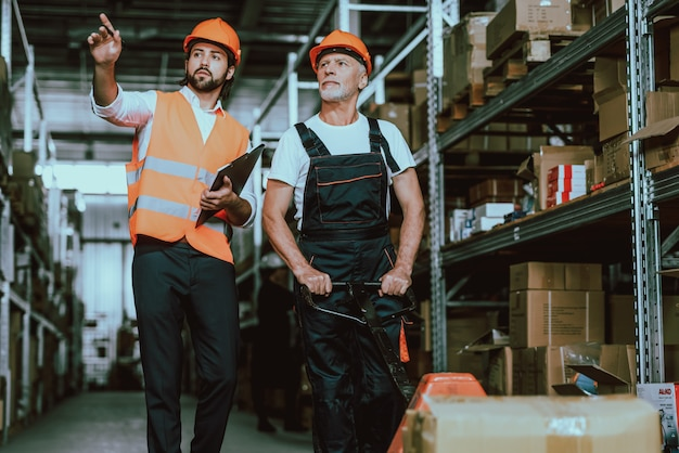 Manager in hardhat talking with warehouse worker