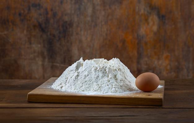 Manciata di farina con l'uovo marrone sulla tavola di legno