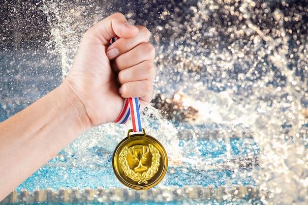 Manciata di medaglia d'oro dell'uomo asiatico con sfondo sfocato della piscina e della concorrenza nuziale.