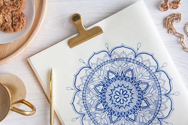 Mandala floreale rotondo decorativo disegnato su un foglio bianco. casa relax, hobby e riposo. caffè e biscotti su uno sfondo bianco.