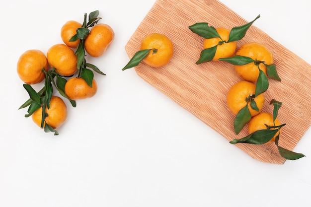 Mandarini con foglie su bianco