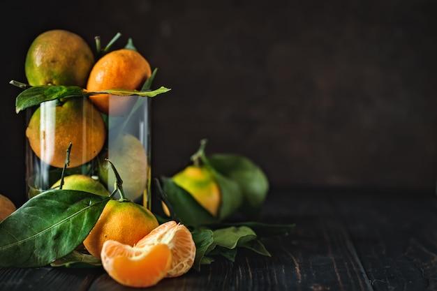 Mandarini con foglie su un vecchio tavolo di campagna
