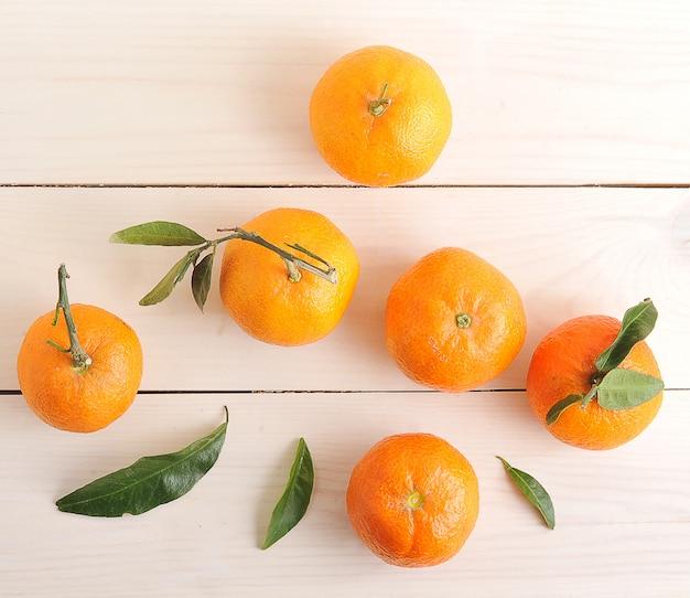 Mandarini con foglie verdi su superficie di legno