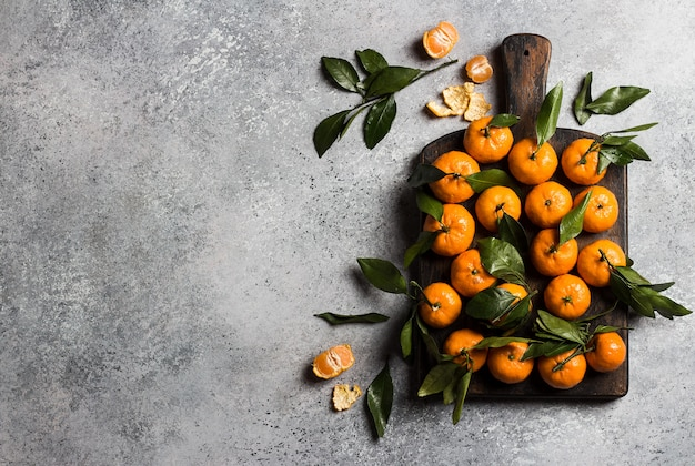 Mandarini con foglie verdi sul bordo di legno sulla luce