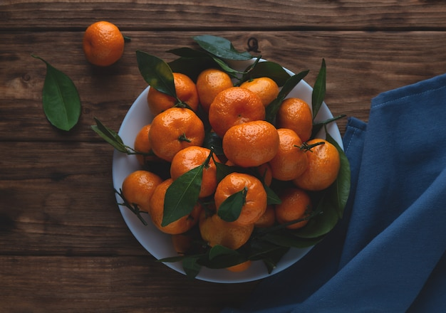 Mandarini con le foglie in un piatto su un fondo di legno.