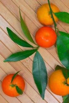 Mandarini con rami verdi su un tavolo di legno