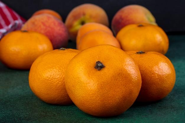 Mandarini di vista frontale con le pesche su verde