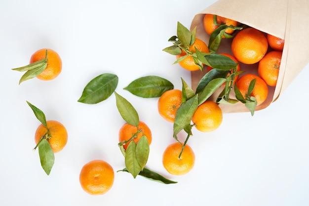 Mandarini freschi arancioni con foglie verdi in un sacchetto di carta