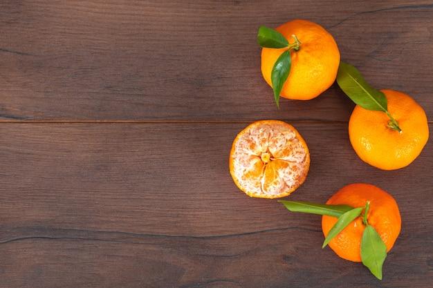 Mandarini freschi con la vista superiore delle foglie con lo spazio della copia sulla tavola marrone