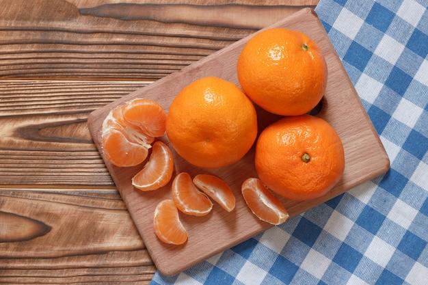 Mandarini freschi di vista superiore sul tavolo con la tovaglia