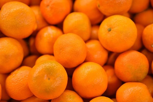 Mandarini gialli freschi di cibo, sfondo. modello arancione fresco per la vendita nel mercato