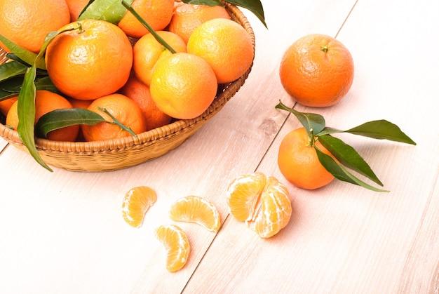 Mandarini nel cestino sulla tavola di legno della cucina