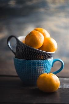 Mandarini organici nella tazza sulla tavola di legno come concetto di inverno