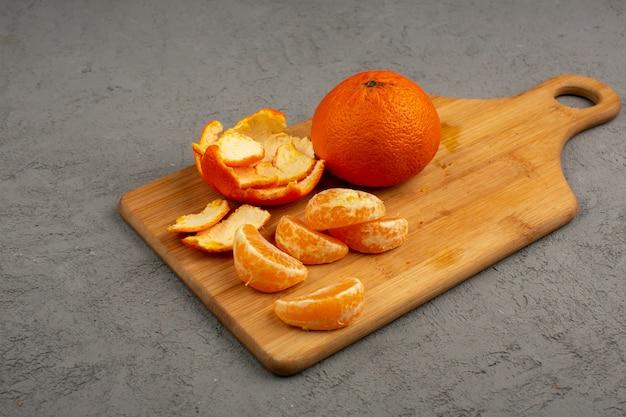 Mandarini pelati insieme a frutta intera e affettata su una scrivania marrone
